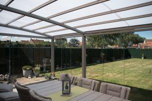 Dichtgebouwde terrasoverkapping met glazen schuifwanden